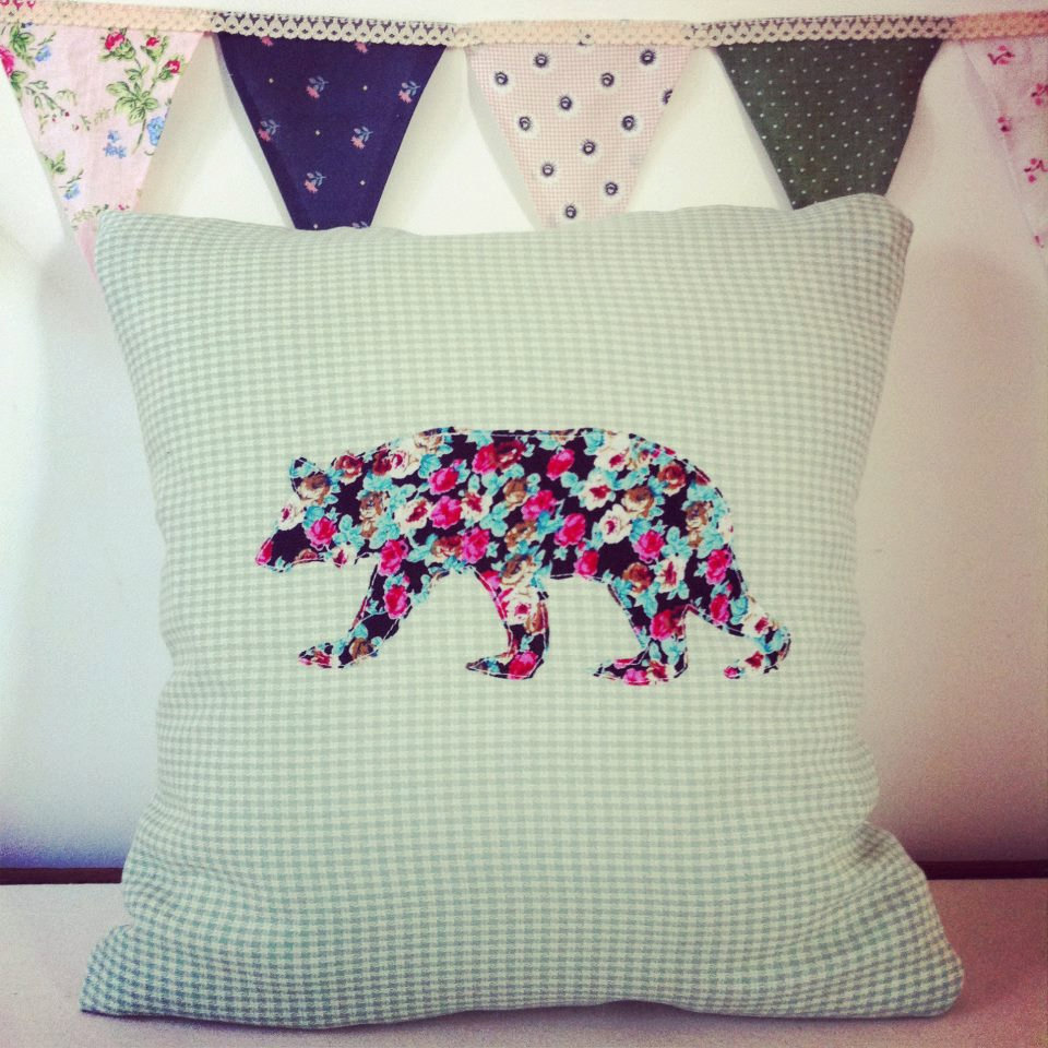 Silhouette of a floral bear on a mint green checked handmade cushion.